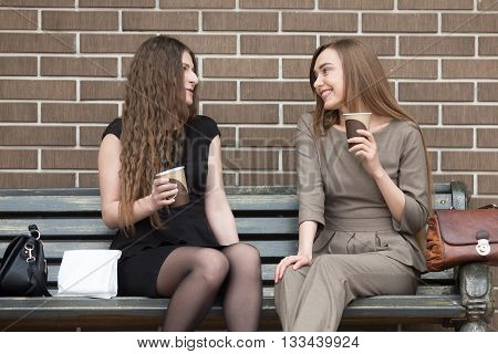 Two Young Beautiful Women Holding Take Away Coffee And Chatting On Bench