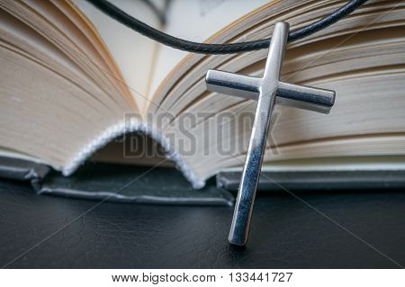Metallic crucifix and opened Holy Bible. Religion concept.