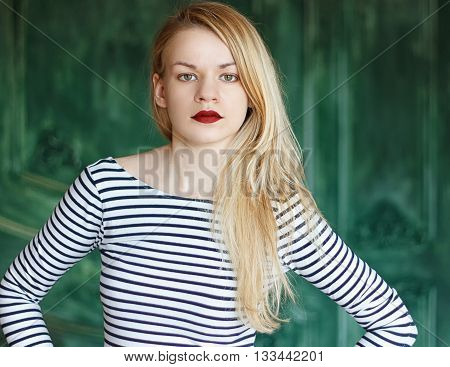 Blonde with red lips in a striped shirt on a green background a grunge wall