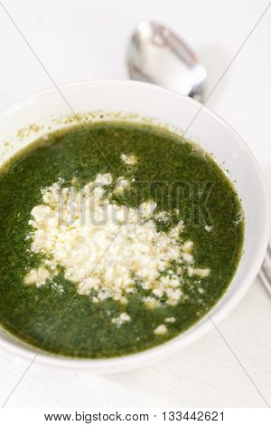 Spinach soup with feta cheese and eggs shot from above. Vertical shot