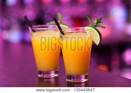 Two Harvey Wallbanger cocktail shot on a bar counter in a night club. Blurred bottles on background. Horizontal shot