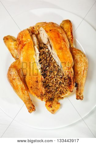 Baked whole chicken stuffed with rice. Shot from above. Vertical shot.