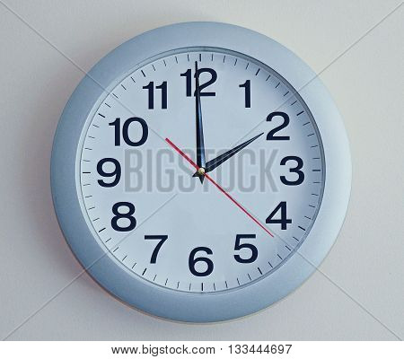 Wall Clock.  Light blue clock with arrows.