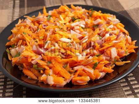 Healthy salad from grated carrots ham and dressing. Horizontal shot full length view.