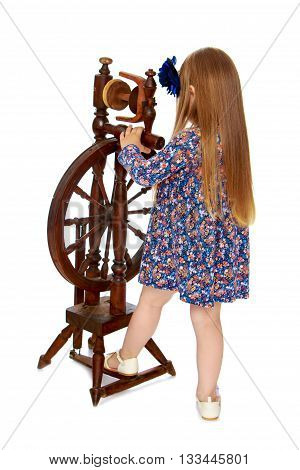little girl looks at an ancient spinning wheel-Isolated on white background