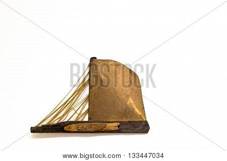 Isolated on light background decorative handmade sailboat out of wood yarn and metal in a retro style weighs on wall. Bali, Rethymno, Crete, Greece