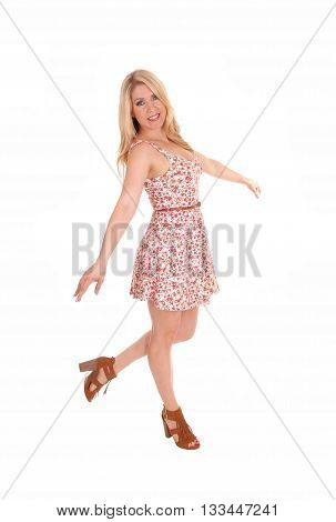 A lovely woman with long blond hair standing in a summer dress isolated for white background looking into the camera.