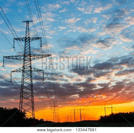 Silhouettes high voltage electric pylon in sunset background.