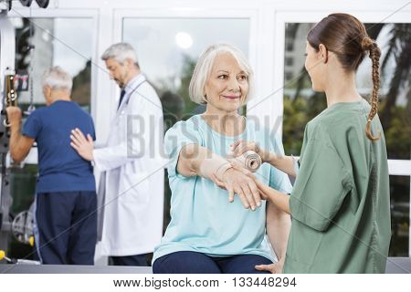 Patient Looking At Nurse Putting Crepe Bandage On Hand