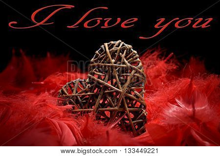 wooden heart in the midst of red feathers on a black background and i love you written
