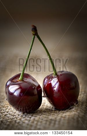 fresh cherries with water drops on jute