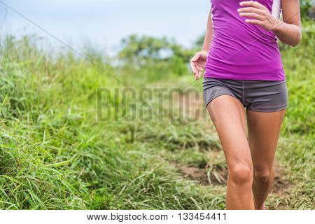 Healthy active woman runner running in outdoor grass nature park trail path. Midsection lower body of girl athlete training cardio. Feminine health care issues: menstrual period pain, stomach problem.