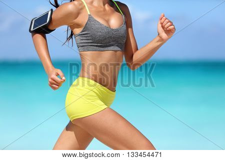 Running fitness woman runner wearing phone armband fast with speed. Hot girl midsection showing muscular legs and motion during intense cardio workout. Woman listening to music over wireless earphones