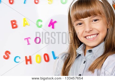 Portrait of a adorable little girl in school in front of whiteboard. Back to school.