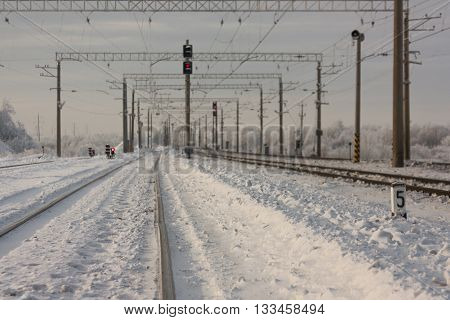 Electrified railway tracks with red railway signals - railway station  in winter period