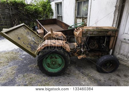 Old vintage tractor rusting away outside near the village house