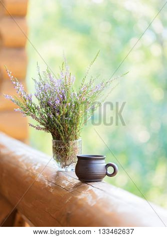 Clay cup with coffee and  bouquet of  heathers on the railing of the balcony. Selective focus. Shallow depth of field.
