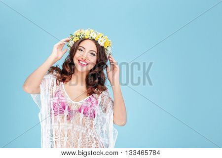 Smiling sexy young brunette woman in a pink bikini wearing flower diadem isolated on the blue background