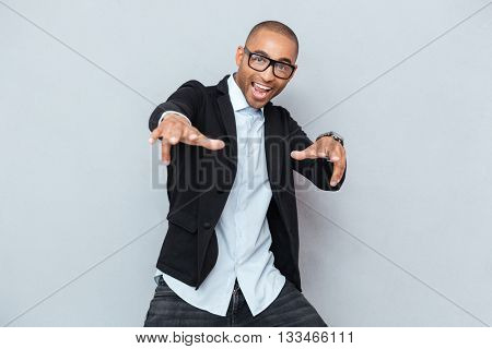 Young handsome stylish man dancing and singing isolated on the gray background