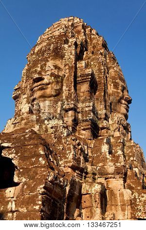 Stone carved face of Bayon Temple in Angkor Thom Angkor district Siem Reap Cambodia