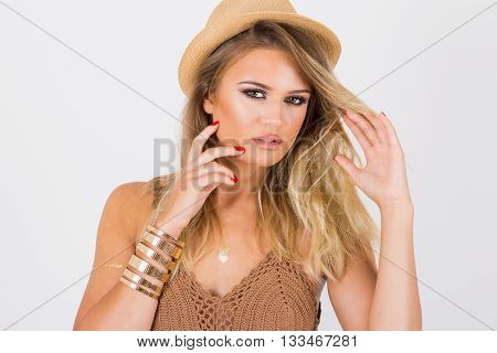 Closeup of gorgeous teenage blonde Caucasian girl in brown crochet crop top with fringes, straw fedora hat and golden bracelet and flash tattoo. No retouch, no filter, studio lighting.