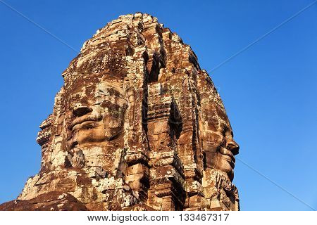 Stone carved faces of Bayon Temple in Angkor Thom Angkor district Siem Reap Cambodia. Horizontal shot sky on background