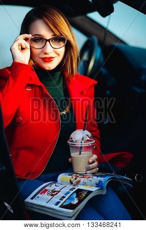 Lifestyle portrait of a remarkable young woman posing with glasses for vision. Girl Drinking coffee and reading a magazine, sitting in the car. Dressed in a bright coat and denim outfit