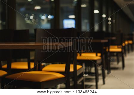 rows of tables and chairs in empty cafe. Close-up