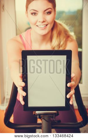 Active young woman working out on exercise bike stationary bicycle holding pc tablet computer with blank screen copyspace. Sporty girl training at home. Fitness and weight loss advertisement concept.
