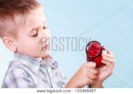 Early education nature and biology discovery. Little boy examine fruit apple with magnifying glass.