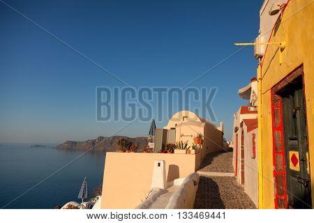 Narrow street and sea view in Oia Santorini at sunrise