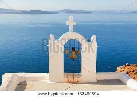 Church bell in Oia Santorini Greece. Sea and volcano on background. Horizontal shot