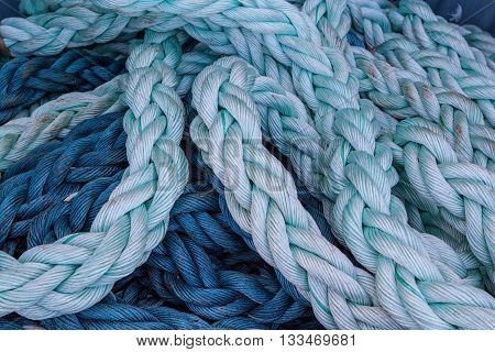 Close-up of an old blue boat rope as a nautical background.