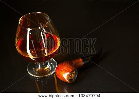 Whiskey glass and smoking pipe on black background. Cognac glass. Brandy glassful. Cognac france. Scotch drink. Smoking pipe.