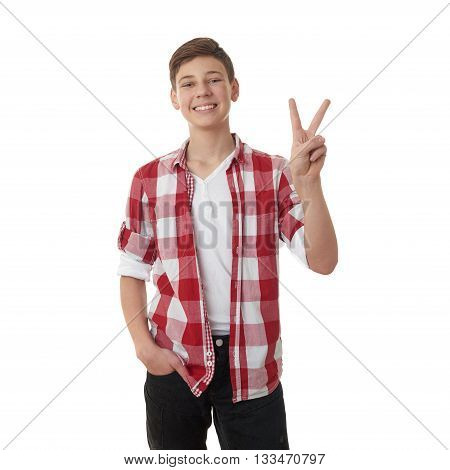 Cute teenager boy in red checkered shirt showing victory sign over white isolated background, half body