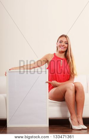 Cute attractive young woman girl in red shirt on sofa couch with blank empty white copy space banner. Summer female fashion vogue and advertisement.