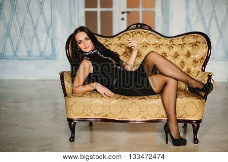 Elegant woman in black dress sitting on chesterfield armchair in classic vintage interior. Glamour