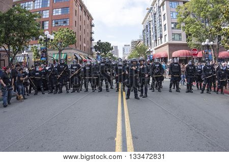 SAN DIEGO USA - MAY 27 2016: Riot police in full riot gear stand in position ready to march down San Diego's Fifth Avenue to disperse a crowd of hundreds of protesters and Trump supporters outside a Trump rally.