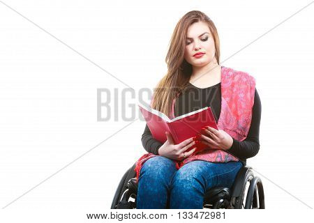 Studying and reading concept. Disabilty and handicap. Young disabled woman on wheelchair reads book.
