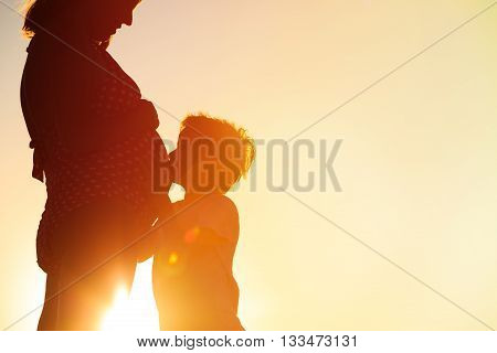 Silhouette of little boy hugging pregnant mother tummy at sunset beach