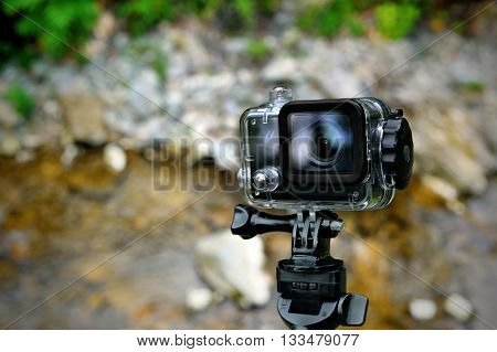 Action waterproof camera on mountain river background