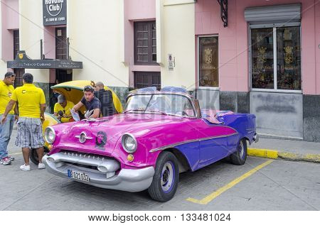 HAVANA - NOVEMBER 29: American classic car waiting for tourists on 29 November 2015 in Havana, Cuba. Brightly colored vintage American cars are very popular in Havana.