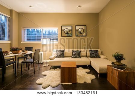 Modern living and dining room interior design with sofa and table set for dinner.