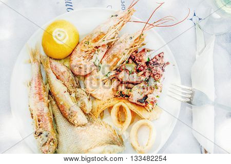Cooked seafood on plate with lemon and wine. Prawns, squid, octopus, mullet fish and seabream. Traditional Mediterranean dish on Greek island of Kastelorizo