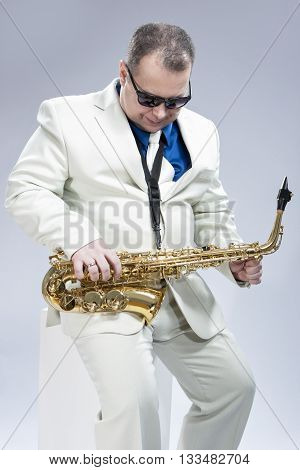 Music Concept and Ideas. Handsome Caucasian Musician with Saxophone Posing in White Siut Against Gray. Vertical Image