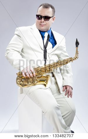 Music Concept. Portrait of Handsome Caucasian Musician With Alto Saxophone Posing In White Suit Against White Background. Wearing Black Sunglasses.Vertical Image Composition