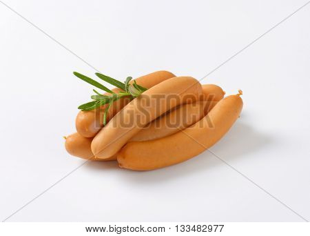 thin wiener sausages with rosemary on white background