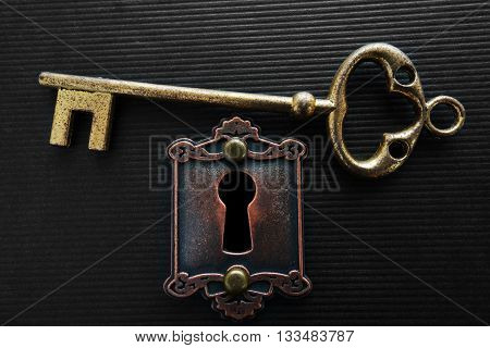 Vintage gold key and an old lock