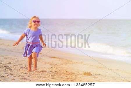 little girl run on sand beach, family vacation