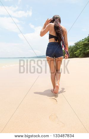 Young Asian woman on vacation leaves footsteps as she walks in the sand on a tropical paradise beach, back view. Travel, vacations and discovery.